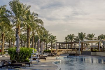 A swimming pool surrounded by palm trees in Bahrain, representing things to pay attention to when renting an apartment in Bahrain